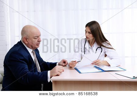 Young female doctor receiving patient in her office
