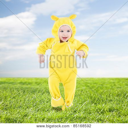 people, children, achievement and happiness concept - happy baby in yellow suit making first steps over blue sky and grass background