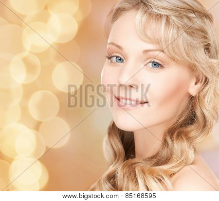 beauty, people, hair care and health concept - beautiful young woman face with long wavy hair over beige lights background