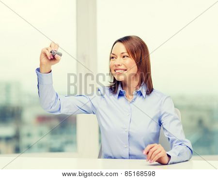 office, business, technology concept - businesswoman writing something in the air with marker