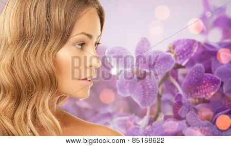 beauty, people and health concept - beautiful young woman face over purple orchid flowers background