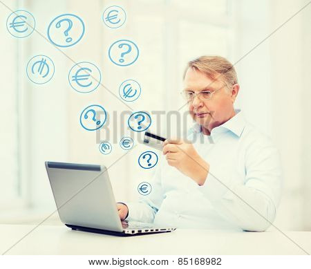 business, online banking, internet shopping and oldness concept - smiling old man with laptop computer and credit card at home