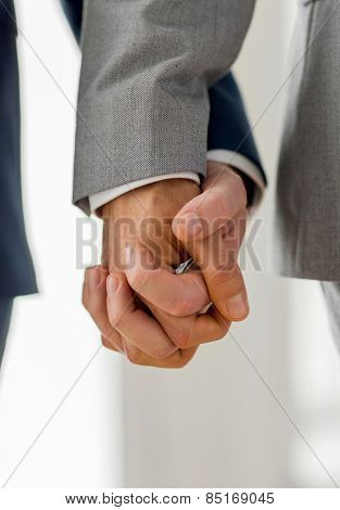 people, homosexuality, same-sex marriage and love concept - close up of happy male gay couple holding hands