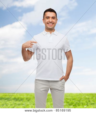 happiness, advertisement, fashion, gesture and people concept - smiling man in t-shirt pointing finger on himself over blue sky and grass background
