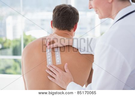 Doctor doing skin test to her patient in medical office