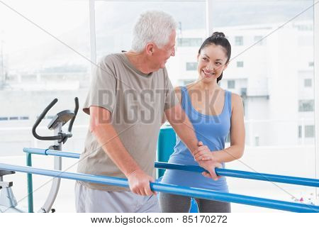 Senior man walking with trainer in fitness studio