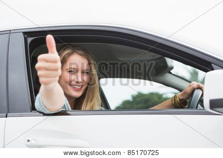Happy woman sitting in drivers seat thumb up in her car