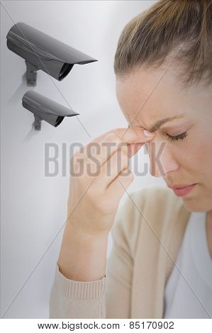 Woman with headache against cctv camera