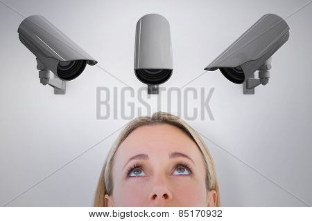 Close up of blonde woman looking up against cctv camera