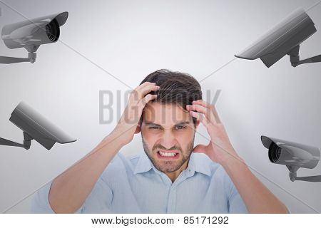 Stressed man looking at camera against cctv camera