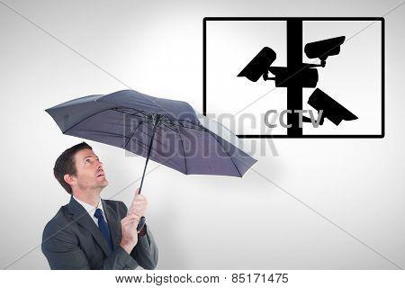 Businessman sheltering under black umbrella against cctv
