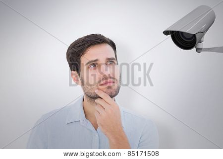 Serious thinking man looking up against cctv camera
