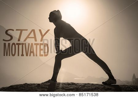 Sporty blonde stretching on the beach on a rock against stay motivated