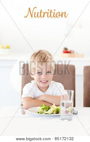 The word nutrition against cute little boy ready to eat his salad for lunch sitting at a table