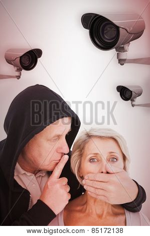 Older man silencing his fearful partner against cctv camera