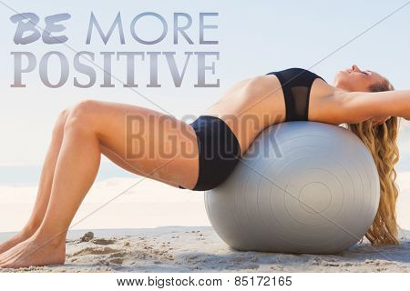 Fit blonde stretching her back on exercise ball at the beach against be more postive