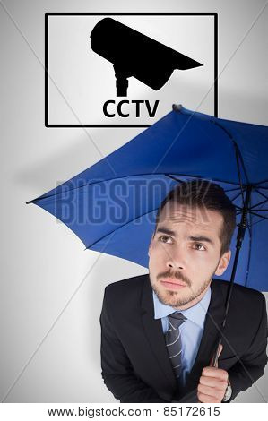 Anxious businessman under umbrella looking up against cctv