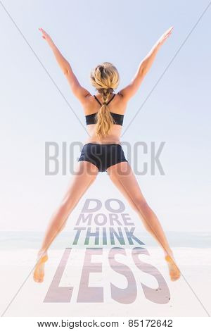 Fit blonde jumping on the beach with arms outstretched against do more think less