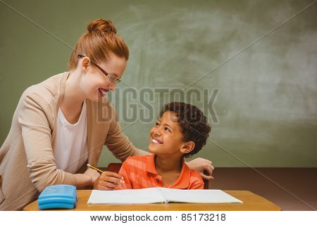 Portrait of teacher assisting little boy with homework in the classroom