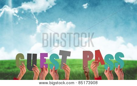 Hands holding up guest pass against blue sky over green field