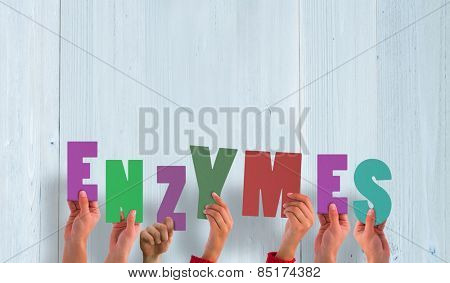 Hands holding up enzymes against wooden planks