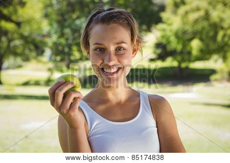Fit woman holding green apple on a sunny day