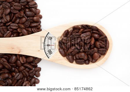 weighing scales against wooden spoon with coffee seeds