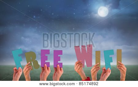 Hands holding up free wifi against green field at night