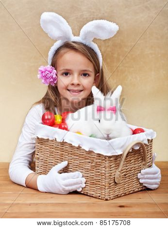 Happy spring girl with easter basket - holding colorful eggs and white rabbit