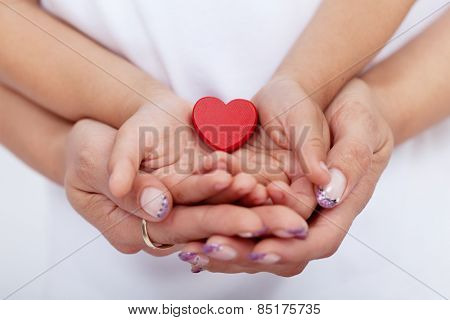 Adult and child hands holding red heart together-shallow depth of field