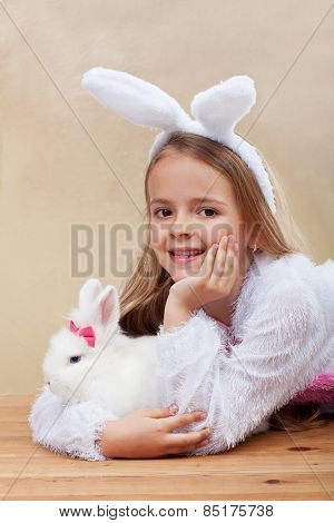 Happy girl in bunny costume holding her white rabbit - laying on wooden floor