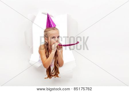 Little party girl with hat and whistle looking out on blast hole in paper - with copy space