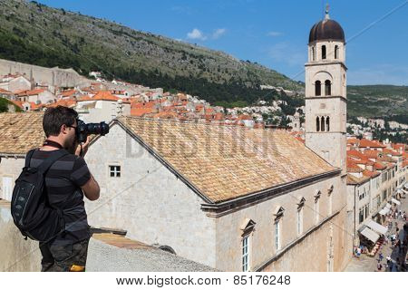DUBROVNIK, CROATIA - MAY 26, 2014: Young photographer taking photos of Stradun from Old city walls. Stradun is 300 meters long main pedestrian street in Dubrovnik.