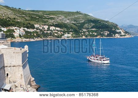 DUBROVNIK, CROATIA - MAY 26, 2014: Tourist boat in the bay near Old city walls.  The wall is one of Dubrovnik's most famous feature.