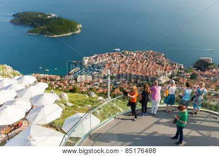 DUBROVNIK, CROATIA - MAY 26, 2014: Tourists at viewpoint at cable car station which connects Ploce and mountain Srdj above town with a panoramic view of Old Town and the surrounding islands.