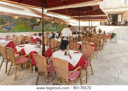 DUBROVNIK, CROATIA - MAY 26, 2014: Waiter setting up  tables at restaurant terrace. Dubrovnik has many restaurants which offer traditional Dalmatian cuisine and some great wine lists.