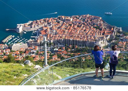 DUBROVNIK, CROATIA - MAY 26, 2014: Tourists at viewpoint at cable car station which connects Ploce and mountain Srdj above town and enjoy a panoramic view of Old Town and the surrounding islands.