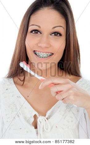 Attractive young woman with brackets cleaning her teeth isolated on a white backgroung