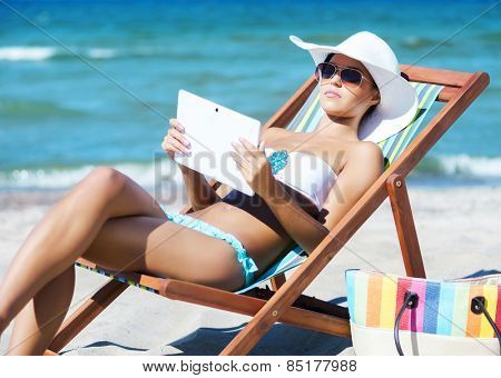 A young woman relaxing with a tablet computer on a beautiful beach