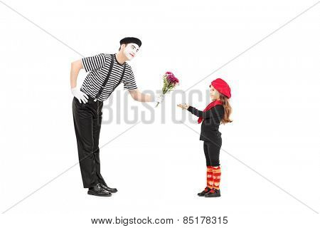 Full length portrait of a mime artist giving flowers to a little girl isolated on white background