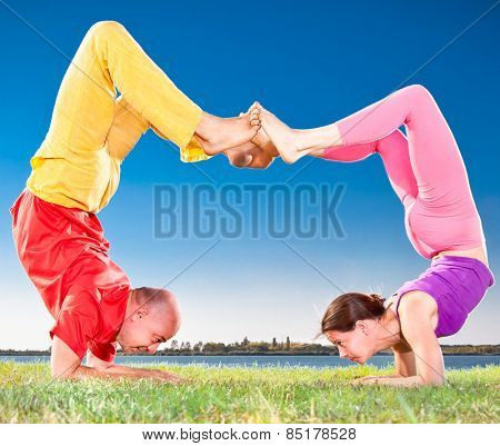Yoga couple, man and woman doing Vrschikasana scorpion pose on lake bench. Yoga concept.