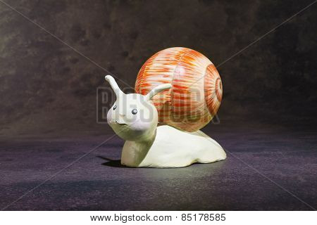 ceramic puppet handmade, one snail, gray background