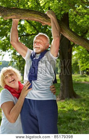 Old man doing pull-ups on a tree in a summer park