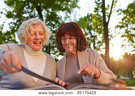 Two happy senior women reading a cookbook in a garden
