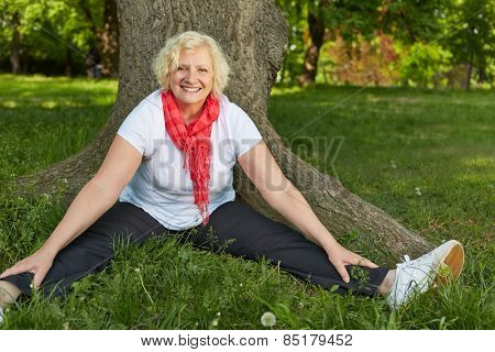 Happy senior woman doing back training in nature in a park