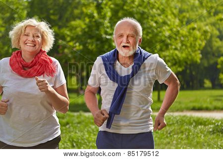 Two happy senior people jogging in a park in summer