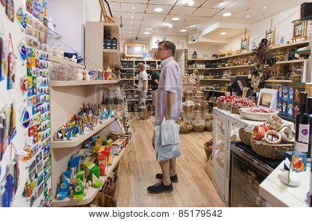 DUBROVNIK, CROATIA - MAY 28, 2014: Tourist browsing in the souvenir shop.