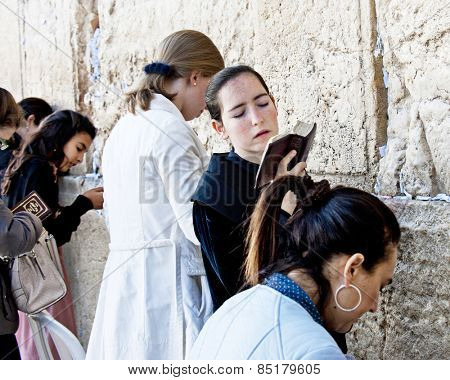 JERUSALEM, ISRAEL - OCTOBER 31, 2014:  Women praying at female side of Jerusalem's Western Wall.  Focus is on the center woman with prayer book.  She is twisting from side to side with closed eyes.