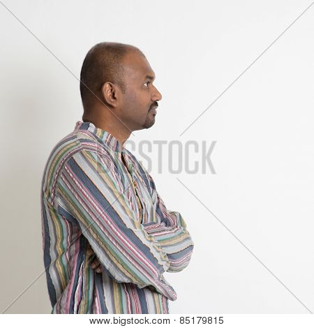 Profile of Indian male looking at blank copy space having a thought on plain background.