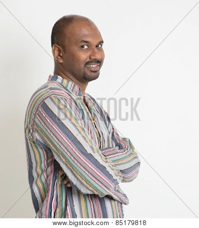 Portrait of smiling Indian man arms crossed looking at camera on plain background with shadow